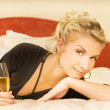 Beautiful young lady lying in a bed with a glass of champagne — Stock Photo