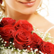 Luxury bridal bouquet and happy bride&#039;s face fragment - 