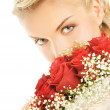 Beautiful bride hiding behind luxury bouquet of roses - 