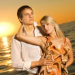 Young couple in love near the ocean at sunset - Foto Stock