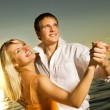Young couple dancing near the ocean at sunset — Stock Photo #4791425