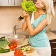 Beautiful young woman making vegetarian vegetable salad - Stock Photo