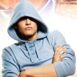 Cool looking man in a hood over abstract graffity background — Stock Photo
