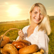 Beautiful young woman with a basket full of fresh baked bread — Stock Photo #4791501