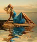 Sexy young woman flapping her blond hair near the ocean — Stock Photo
