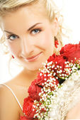 Beautiful bride hiding behind luxury bouquet of roses — Stock Photo
