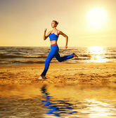 Beautiful young woman running on a beach at sunset — Stock Photo