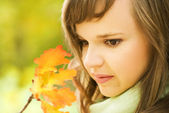 Beautiful brunette with autumn leaves close-up portrait — Stock Photo