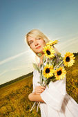 Young beautiful woman with a bouquet of sunflowers in the field — Stock Photo