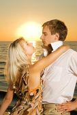 Aşık genç bir çift okyanus günbatımında yakınındaki — Stok fotoğraf