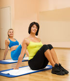 Two beautiful women doing fitnees exercise in a sport club — Stock Photo