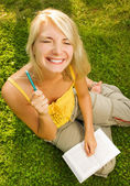 Funny wide angle portrait of a young woman reading book outdoors — Stock Photo
