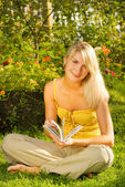 Happy young woman readin book in a park — Stock Photo