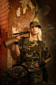 Beautiful woman soldier with a sniper rifle — Stock Photo