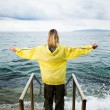 Brave woman greeting stormy ocean — Stock Photo #4800437