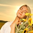 Young beautiful woman with a bouquet of sunflowers in the field — Stock Photo #4800446