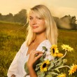 Young beautiful woman with a bouquet of sunflowers in thr field — Stock Photo #4800448