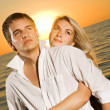 Stock Photo: Young couple in love near the ocean at sunset