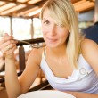 Young woman eating tomato soup in a restaurant — Stock Photo
