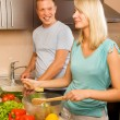 Young couple making vegetable salad in the kitchen — Stok fotoğraf