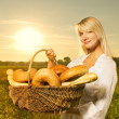 Beautiful young woman with a basket full of fresh baked bread - Photo