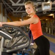Beautiful young woman doing exercise in a gym while listening to — Stock Photo #4800541