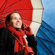 Beautiful brunette with red umbrella talking on the phone — Stock Photo #4800547