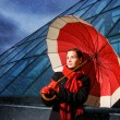 Beautiful young woman with red umbrella on rainy day — Stock Photo #4800548