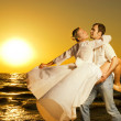 Beautiful young couple dancing on the beach at sunset — Stock Photo