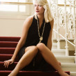 Lovely blond lady sitting on a red carpet — Stock Photo #4800661