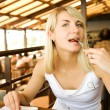 Beautiful young woman eating vegetarian food in a restaurant — Stock Photo