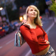 Beautiful young woman in a city at night — Stock Photo