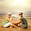 Two beautiful women sitting on the beach - Stock Photo
