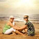 Two beautiful women sitting on the beach — Stock Photo #4800697