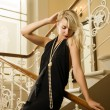 Beautiful young woman standing on a staircase — Stock Photo