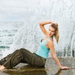 Wet girl sitting near the ocean. Wall of water behind her — Stock Photo #4800703