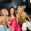 Three beautiful women in a limousine - Stock Photo