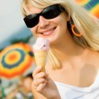 Beautiful young woman eating ice-cream on the beach — Stock Photo