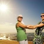 Two beautiful women sitting on the beach — Stock Photo #4803854