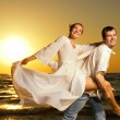 Young couple having fun near the ocean at sunset — Stock Photo #4803855