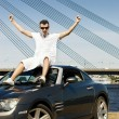 Happy young man sitting on top of his modern sport car — Stock Photo