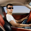 Handsome young man driving modern sport car - Stock Photo