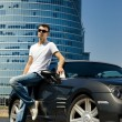Handsome man standing near the modern sport car — Stock Photo
