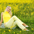 Beautiful young woman sitting in a flower field — Stock Photo #4803872