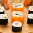 Different types of sushi on a bamboo plate — Stock Photo