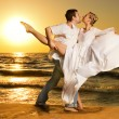 Beautiful young couple dancing tango on the beach at sunset — Stockfoto