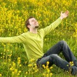Happy young man sitting in a flower field — Stock Photo