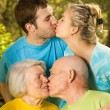 Young and senior couples kissing outdoors — Stock Photo