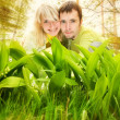 Young couple hiding in fresh green grass — Stock Photo
