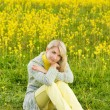 Beautiful young woman sitting in a flower field — Stock Photo #4804036